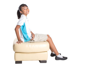 Young Asian school girl in uniform sitting on a couch