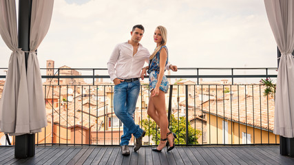 Beautiful casual young couple portrait outdoors in hotel terrace