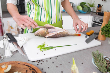 Woman in the kitchen preparing fish dinner with perch.