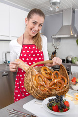Young woman presenting a basket with fresh bavarian pretzels.