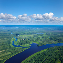 Forest river under white clouds, top view
