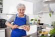 Happy senior woman in the kitchen preparing fresh fish.