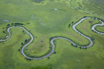 aerial view over the small river on the green grassland