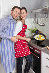 Young fresh married couple in the kitchen cooking together fried