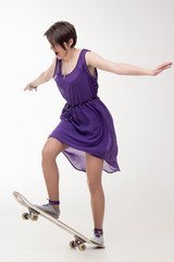 Teenage girl in dress on skateboard
