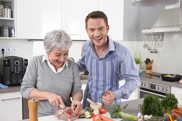 Hotel mama: young man and older woman cooking together pork.