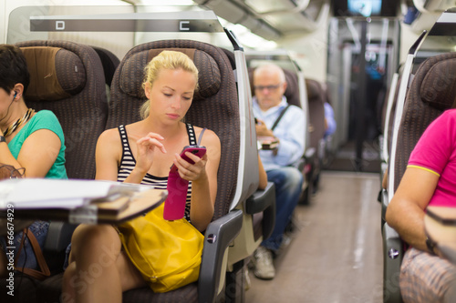 Lady traveling by train using smartphone. - 66674929