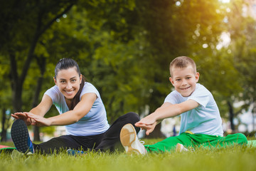 son and mother are doing exercises in the park