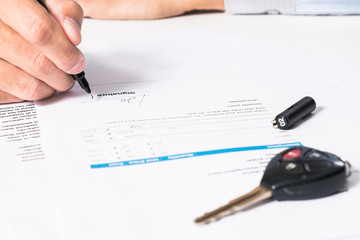 signing pen and car key for Vehicle Sales Agreement