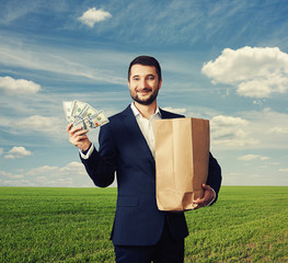 man holding paper bag and money