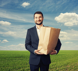 man holding paper bag over green field
