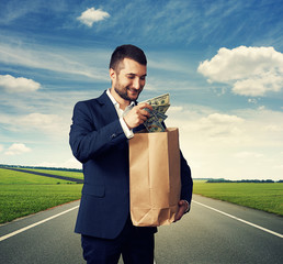 man with paper bag and money