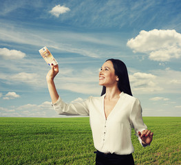 smiley woman looking at banknote