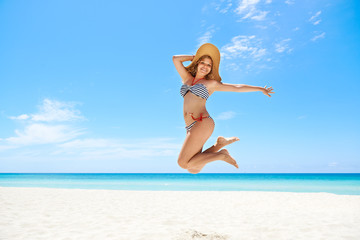 Woman with straw hat jumping mid-air at beach