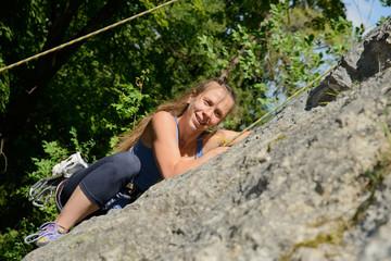 young woman climbing a rock wall