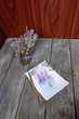 on a wooden table is a vase with a bouquet of lavender and paint