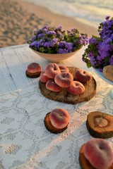 on a wooden table scattered ripe peaches and a bouquet of flower