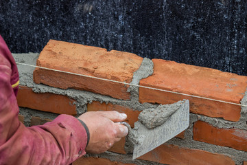 Builder worker using the sharp end of the trowel