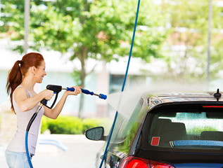 Happy Young woman washing her black car at self service station