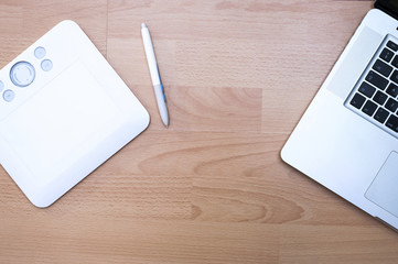 White graphic tablet with a pen and laptop on wooden background