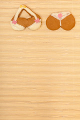 Yellow pink bikini shape gingerbread cake cookie on bamboo mat