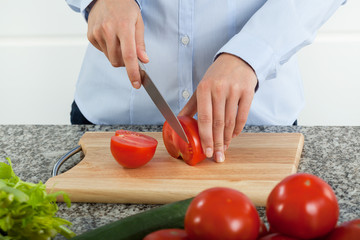 Cutting fresh red tomatoes on cutting board