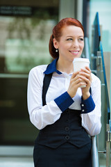 Happy lawyer drinking coffee outside her office