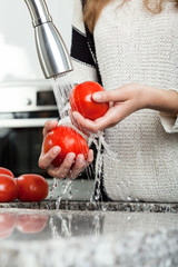 Washing tomatoes under the tap
