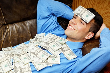 Young businessman lying on the couch and relaxes with money