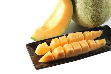 slices cantaloupe melon fruit in blackdish.