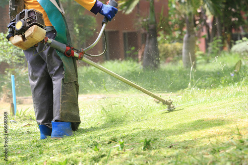 lawn mower worker cutting grass in green field - 66688169