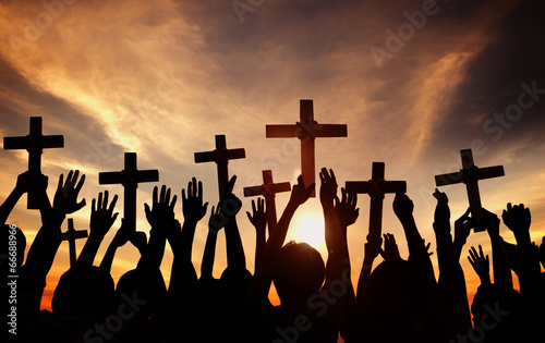 Group of People Holding Cross and Praying in Back Lit - 66688966