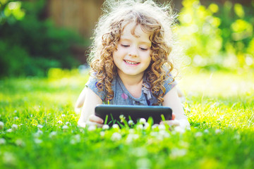 Charming curly girl lying on the grass and holds in hands tablet