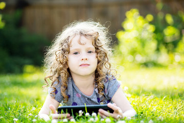 Little curly girl lying on the grass and holds in hands tablet.