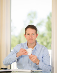 Mature Man enjoying coffee while at work