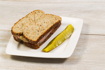 Fresh Ham Sandwich with Sliced Pickle on White Plate