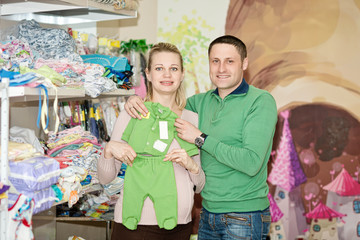 Pregnant woman buying baby clothes in supermarket .  Young pregn