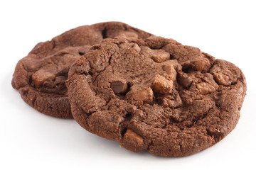 Two dark large chocolate chip cookies on white