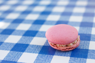Pink macaron sitting on a blue check pattern table cloth.