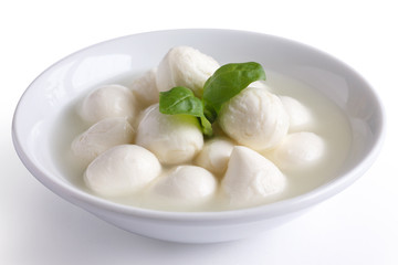 Small white mozzarella balls in a white dish with liquid.