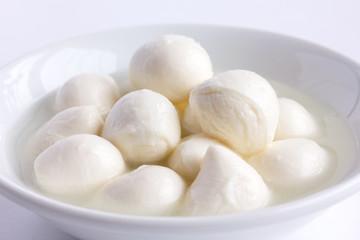 Small white mozzarella balls in a white dish with liquid.