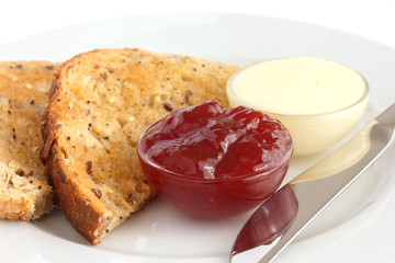 Slice of multi-seed wholegrain bread toasted with butter and jam