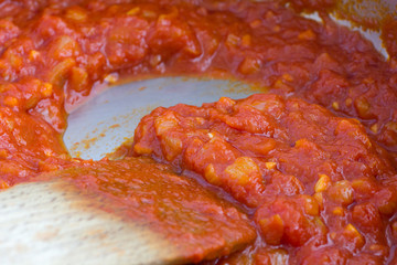 Freshly cooked tomato sauce in a pan with wooden spoon.