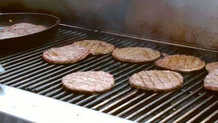 flipping barbecue burgers over on flaming grill
