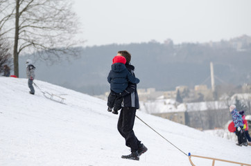 father with son climb up snowy hill in winter time
