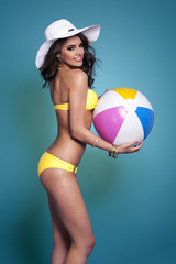 Lovely smiling woman holding beach ball