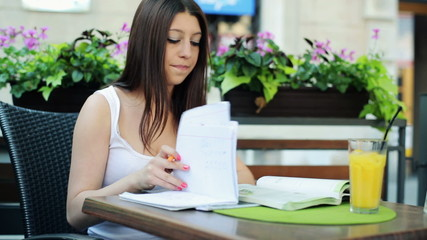 Young sad student overwhelmed by her homework in cafe