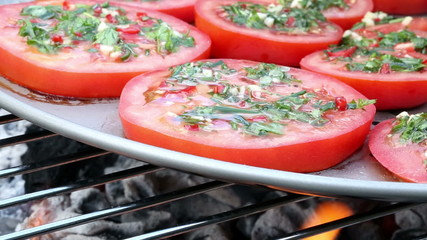 Tomato slices with herbs frying in a pan on a barbecue grill