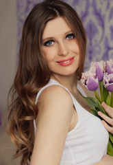 Beautiful pregnant woman with tulips waiting a baby