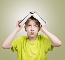 Preteen boy with a book on his head